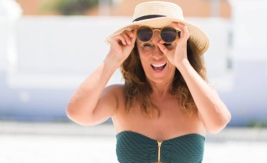 Middle age brunette woman wearing sunglasses on vacations with happy face smiling doing ok sign with hand on eye looking through fingers