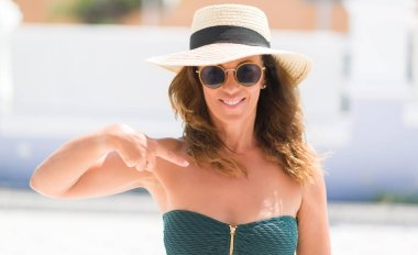Middle age brunette woman wearing sunglasses on vacations with surprise face pointing finger to himself