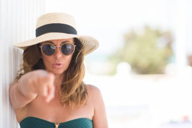 Middle age brunette woman wearing sunglasses and summer hat pointing with finger to the camera and to you, hand sign, positive and confident gesture from the front