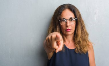 Middle age hispanic woman over grey wall wearing glasses pointing with finger to the camera and to you, hand sign, positive and confident gesture from the front