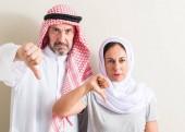 Fotografie Arabské pár středního věku, Žena a muž s naštvaný obličej, záporné znaménko ukazující nechuť s palci dolů, koncept odmítnutí