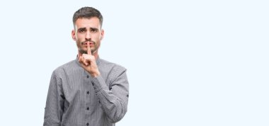 Young hipster man asking to be quiet with finger on lips. Silence and secret concept.