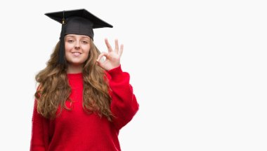Young blonde woman wearing graduation cap doing ok sign with fingers, excellent symbol