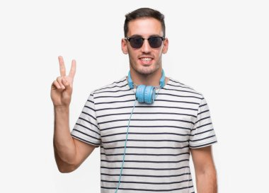Handsome young man wearing headphones showing and pointing up with fingers number two while smiling confident and happy.