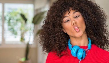 African american woman wearing headphones making fish face with lips, crazy and comical gesture. Funny expression.