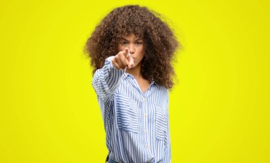 African american woman wearing a stripes shirt pointing with finger to the camera and to you, hand sign, positive and confident gesture from the front