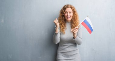 Young redhead woman over grey grunge wall holding flag of Russia screaming proud and celebrating victory and success very excited, cheering emotion