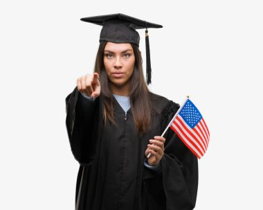 Young hispanic woman wearing graduated uniform holding flag of america pointing with finger to the camera and to you, hand sign, positive and confident gesture from the front