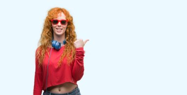 Young redhead woman wearing headphones pointing and showing with thumb up to the side with happy face smiling
