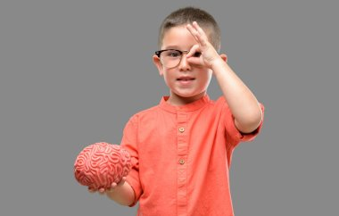 Dark haired little child with glasses holding a brain with happy face smiling doing ok sign with hand on eye looking through fingers
