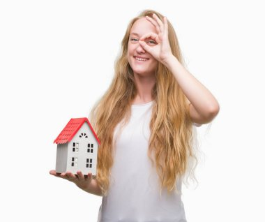 Blonde teenager woman holding family house with happy face smiling doing ok sign with hand on eye looking through fingers