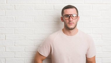 Young caucasian man standing over white brick wall wearing glasses with a confident expression on smart face thinking serious