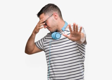 Handsome young man wearing headphones covering eyes with hands and doing stop gesture with sad and fear expression. Embarrassed and negative concept.