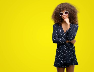 African american woman with sunglasses and summer dress serious face thinking about question, very confused idea