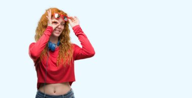 Young redhead woman wearing headphones with happy face smiling doing ok sign with hand on eye looking through fingers