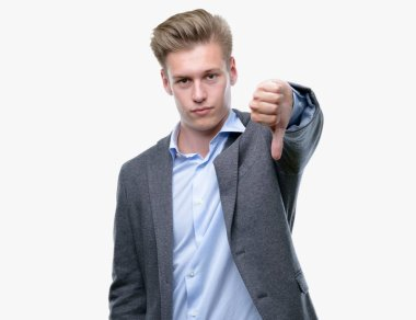 Young handsome blond business man looking unhappy and angry showing rejection and negative with thumbs down gesture. Bad expression.