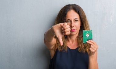 Middle age hispanic woman standing over grey grunge wall holding hard drive with angry face, negative sign showing dislike with thumbs down, rejection concept