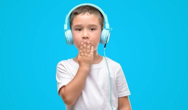 Dark haired little child listening music with headphones cover mouth with hand shocked with shame for mistake, expression of fear, scared in silence, secret concept