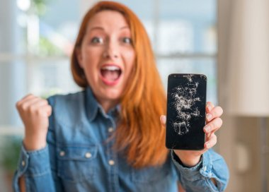 Redhead woman holding broken smartphone screaming proud and celebrating victory and success very excited, cheering emotion