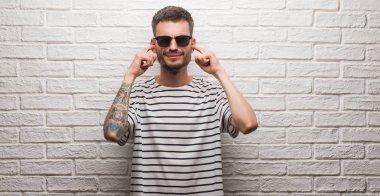 Young adult man wearing sunglasses standing over white brick wall covering ears with fingers with annoyed expression for the noise of loud music. Deaf concept.