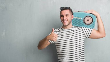 Young caucasian man over grey grunge wall listening music on vintage radio happy with big smile doing ok sign, thumb up with fingers, excellent sign