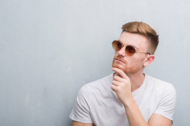 Young redhead man over grey grunge wall wearing retro sunglasses serious face thinking about question, very confused idea