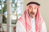 Photo Middle age arabian man at home scared in shock with a surprise face, afraid and excited with fear expression