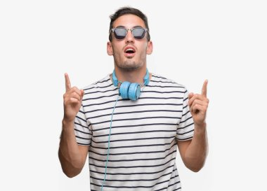 Handsome young man wearing headphones amazed and surprised looking up and pointing with fingers and raised arms.