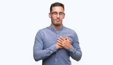 Handsome young elegant man wearing glasses smiling with hands on chest with closed eyes and grateful gesture on face. Health concept.