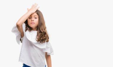 Brunette hispanic girl surprised with hand on head for mistake, remember error. Forgot, bad memory concept.