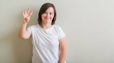 Down syndrome woman standing over wall showing and pointing up with fingers number four while smiling confident and happy.
