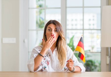 Young woman at home holding flag of Germany cover mouth with hand shocked with shame for mistake, expression of fear, scared in silence, secret concept