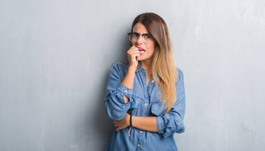 Young adult woman over grunge grey wall wearing glasses looking stressed and nervous with hands on mouth biting nails. Anxiety problem. stock vector