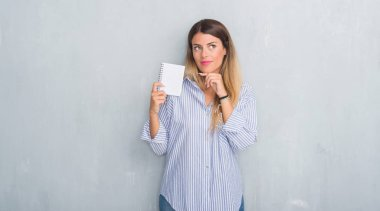 Young adult woman over grey grunge wall holding blank notebook serious face thinking about question, very confused idea