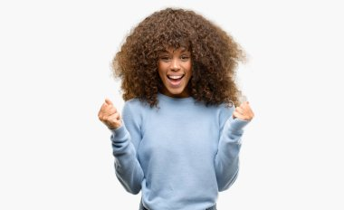 African american woman wearing a sweater celebrating surprised and amazed for success with arms raised and open eyes. Winner concept.