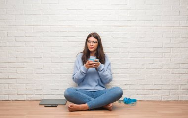Young brunette woman sitting on the floor over white brick wall drinking coffee with a confident expression on smart face thinking serious