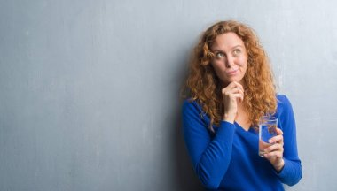 Young redhead woman over grey grunge wall drinking water serious face thinking about question, very confused idea