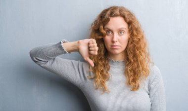 Young redhead woman over grey grunge wall with angry face, negative sign showing dislike with thumbs down, rejection concept