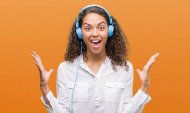 Young hispanic woman wearing headphones very happy and excited, winner expression celebrating victory screaming with big smile and raised hands