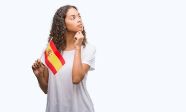 Young hispanic woman holding flag of Spain serious face thinking about question, very confused idea