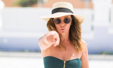 Middle age brunette woman wearing sunglasses on vacations pointing with finger to the camera and to you, hand sign, positive and confident gesture from the front