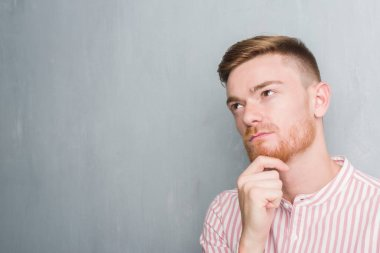 Young redhead man over grey grunge wall serious face thinking about question, very confused idea