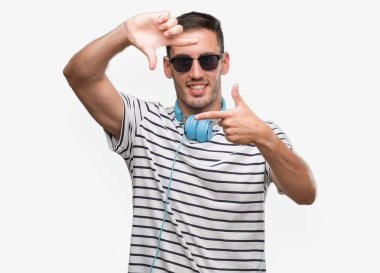 Handsome young man wearing headphones smiling making frame with hands and fingers with happy face. Creativity and photography concept.