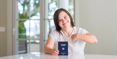 Down syndrome woman at home holding german passport with surprise face pointing finger to himself