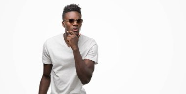 Young african american man wearing sunglasses serious face thinking about question, very confused idea