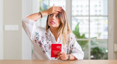 Young woman at home holding a passport of Switzerland stressed with hand on head, shocked with shame and surprise face, angry and frustrated. Fear and upset for mistake.