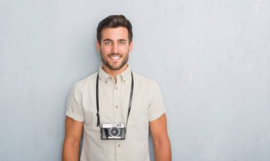 Handsome young man over grey grunge wall holding vintage photo camera with a happy face standing and smiling with a confident smile showing teeth