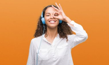 Young hispanic woman wearing headphones with happy face smiling doing ok sign with hand on eye looking through fingers