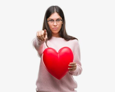 Young hispanic woman holding heart in love pointing with finger to the camera and to you, hand sign, positive and confident gesture from the front