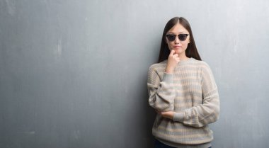 Young Chinese woman over grey wall wearing sunglasses serious face thinking about question, very confused idea